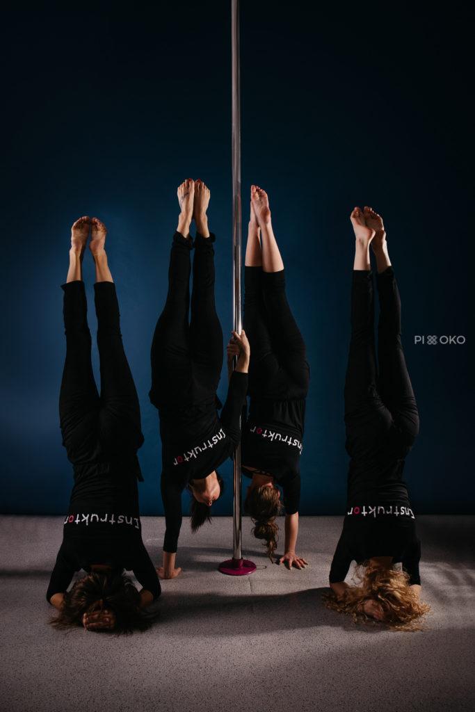 Cztery instruktorki pole dance stojące narękach przy rurze